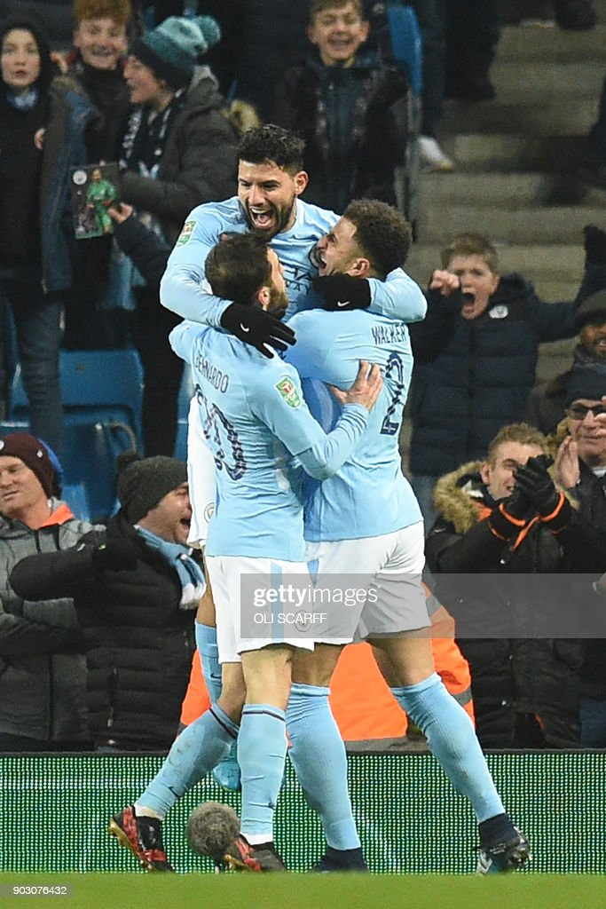 Manchester City's Argentinian striker Sergio Aguero (C) celebrates with teammates after scoring their late winning goal during the English League Cup semi-final first leg football match between Manchester City and Bristol City at the Etihad Stadium in Manchester, north west England, on January 9, 2018. Manchester City won the game 2-1. / AFP PHOTO / Oli SCARFF / RESTRICTED TO EDITORIAL USE. No use with unauthorized audio, video, data, fixture lists, club/league logos or 'live' services. Online in-match use limited to 75 images, no video emulation. No use in betting, games or single club/league/player publications. /