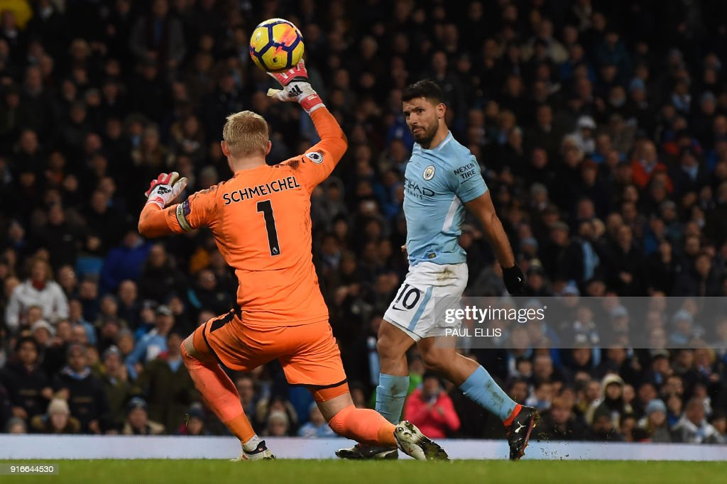 Manchester City's Argentinian striker Sergio Aguero chips the ball over Leicester City's Danish goalkeeper Kasper Schmeichel to score their fourth goal, his third during the English Premier League football match between Manchester City and Leicester City at the Etihad Stadium in Manchester, north west England, on February 10, 2018. / AFP PHOTO / PAUL ELLIS / RESTRICTED TO EDITORIAL USE. No use with unauthorized audio, video, data, fixture lists, club/league logos or 'live' services. Online in-match use limited to 75 images, no video emulation. No use in betting, games or single club/league/player publications. /