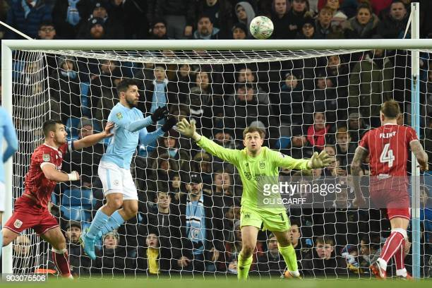 Manchester City's Argentinian striker Sergio Aguero connects with this header to score their late winning goal past Bristol City's English goalkeeper...