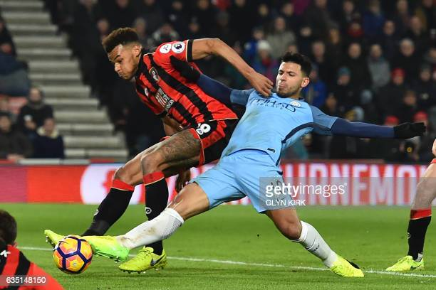 Manchester City's Argentinian striker Sergio Aguero gets his foot to the ball ahead of Bournemouth's English defender Tyrone Mings to score their...