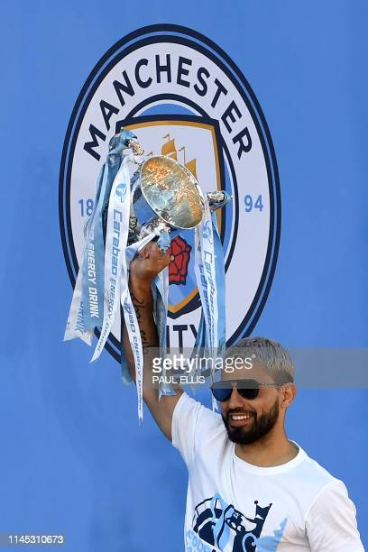 Manchester City's Argentinian striker Sergio Aguero holds aloft the League Cup trophy during a stage presentation following an opentop bus parade...