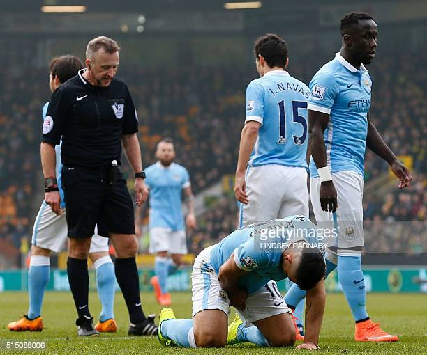 Manchester City's Argentinian striker Sergio Aguero holds his groin as he lays on the pitch following a challenge from Norwich City's German defender...