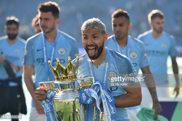 Manchester City's Argentinian striker Sergio Aguero holds the Premier League trophy as City's players celebrate after their 41 victory in the English...