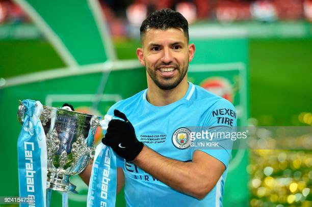 Manchester City's Argentinian striker Sergio Aguero holds the trophy as he poses for a photograph after their victory in the English League Cup final...