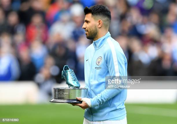 Manchester City's Argentinian striker Sergio Aguero is awarded a trophy for being Manchester City's alltime leading goal scorer ahead of the English...