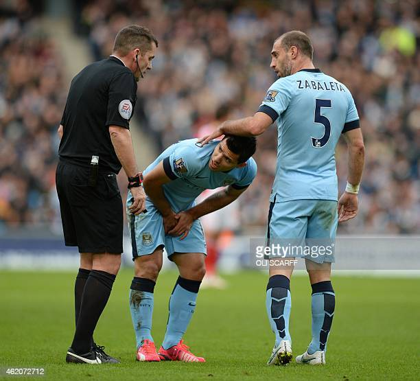 Manchester City's Argentinian striker Sergio Aguero is comforted by Manchester City's Argentinian defender Pablo Zabaleta as he holds his groin...