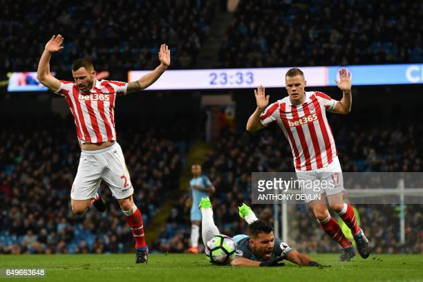 Manchester City's Argentinian striker Sergio Aguero is tripped by Stoke City's Englishborn Scottish defender Phil Bardsley and Stoke City's English...