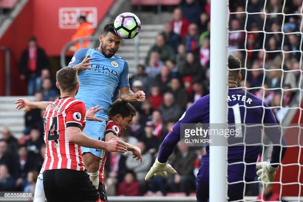 Manchester City's Argentinian striker Sergio Aguero jumps to head their third goal past Southampton's English goalkeeper Fraser Forster during the...