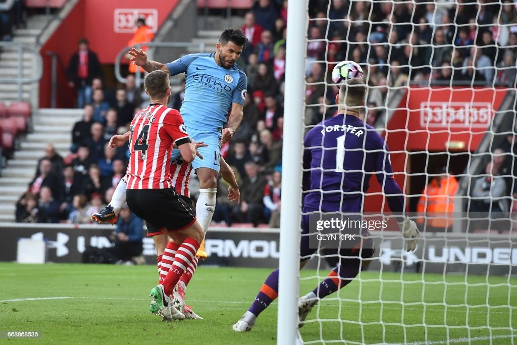 Manchester City's Argentinian striker Sergio Aguero jumps to head their third goal past Southampton's English goalkeeper Fraser Forster (R) during the English Premier League football match between Southampton and Manchester City at St Mary's Stadium in Southampton, southern England on April 15, 2017. / AFP PHOTO / Glyn KIRK / RESTRICTED TO EDITORIAL USE. No use with unauthorized audio, video, data, fixture lists, club/league logos or 'live' services. Online in-match use limited to 75 images, no video emulation. No use in betting, games or single club/league/player publications. /