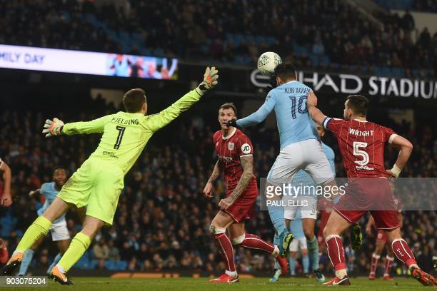 Manchester City's Argentinian striker Sergio Aguero jumps to score their late winning goal during the English League Cup semifinal first leg football...
