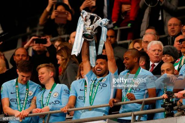 Manchester City's Argentinian striker Sergio Aguero lifts the trophy as Manchester city players celebrate their victory in the English League Cup...