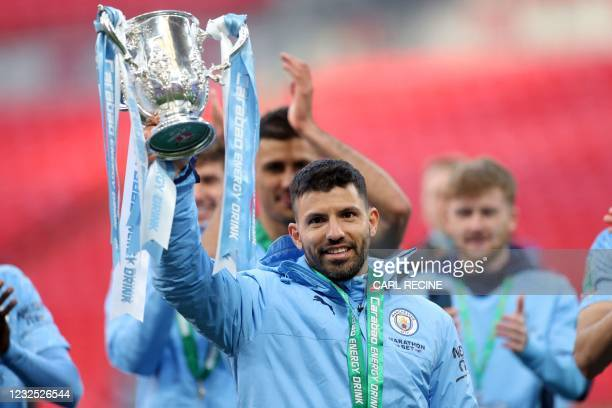 Manchester City's Argentinian striker Sergio Aguero lifts the winners trophy after the English League Cup final football match between Manchester...