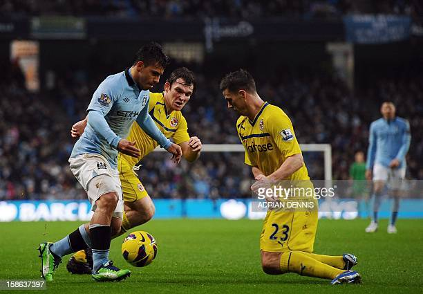 Manchester City's Argentinian striker Sergio Aguero runs with the ball past Reading's English midfielder Jay Tabb and Reading's Irish defender Ian...