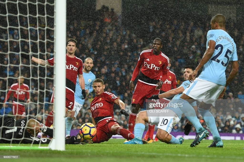 Manchester City's Argentinian striker Sergio Aguero (2R) scores their third goal past Watford's Brazilian goalkeeper Heurelho Gomes (L) during the English Premier League football match between Manchester City and Watford at the Etihad Stadium in Manchester, north west England, on January 2, 2018. / AFP PHOTO / Oli SCARFF / RESTRICTED TO EDITORIAL USE. No use with unauthorized audio, video, data, fixture lists, club/league logos or 'live' services. Online in-match use limited to 75 images, no video emulation. No use in betting, games or single club/league/player publications. /