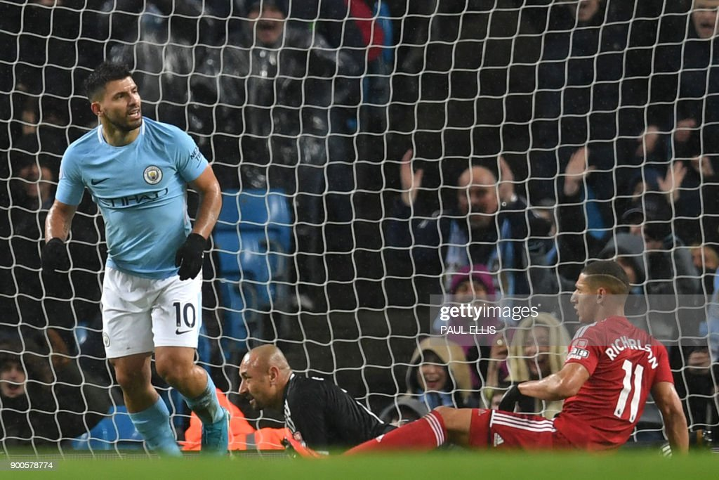 Manchester City's Argentinian striker Sergio Aguero scores their third goal past Watford's Brazilian goalkeeper Heurelho Gomes (2R) during the English Premier League football match between Manchester City and Watford at the Etihad Stadium in Manchester, north west England, on January 2, 2018. / AFP PHOTO / Paul ELLIS / RESTRICTED TO EDITORIAL USE. No use with unauthorized audio, video, data, fixture lists, club/league logos or 'live' services. Online in-match use limited to 75 images, no video emulation. No use in betting, games or single club/league/player publications. /