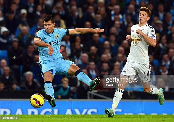 Manchester City's Argentinian striker Sergio Aguero shoots towards goal as Swansea City's English midfielder Tom Carroll tries to stop him during the...