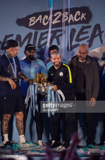 Manchester City's Argentinian striker Sergio Aguero shows the Premier League trophy to supporters outside the Etihad Stadium in Manchester northern...