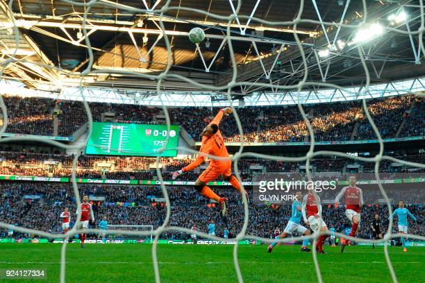 Manchester City's Argentinian striker Sergio Aguero turns to celebrate as his shot loops over Arsenal's Colombian goalkeeper David Ospina for their...