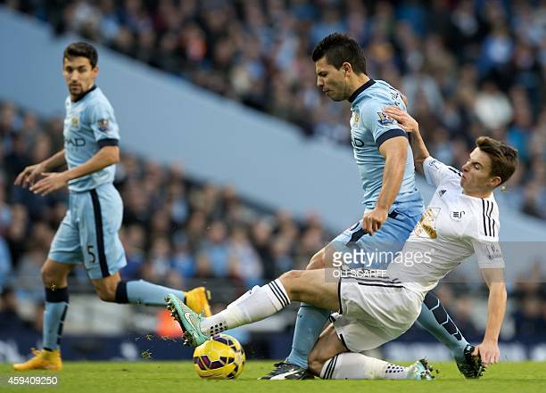 Manchester City's Argentinian striker Sergio Aguero vies for the ball with Swansea City's English midfielder Tom Carroll during the English Premier...