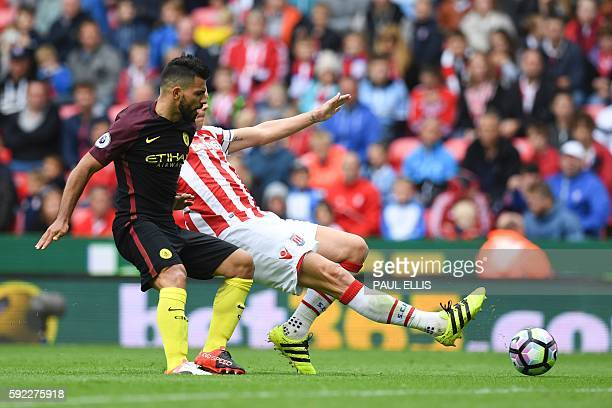 Manchester City's Argentinian striker Sergio Aguero vies with Stoke City's English defender Ryan Shawcross during the English Premier League football...