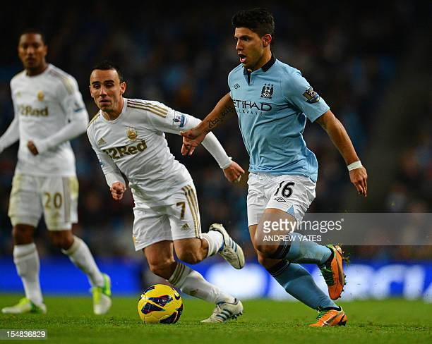 Manchester City's Argentinian striker Sergio Aguero vies with Swansea City's English midfielder Leon Britton during the English Premier League...