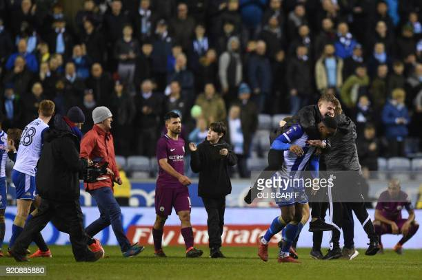 Manchester City's Argentinian striker Sergio Aguero walks as supporters invade the pitch after the English FA Cup fifth round football match between...