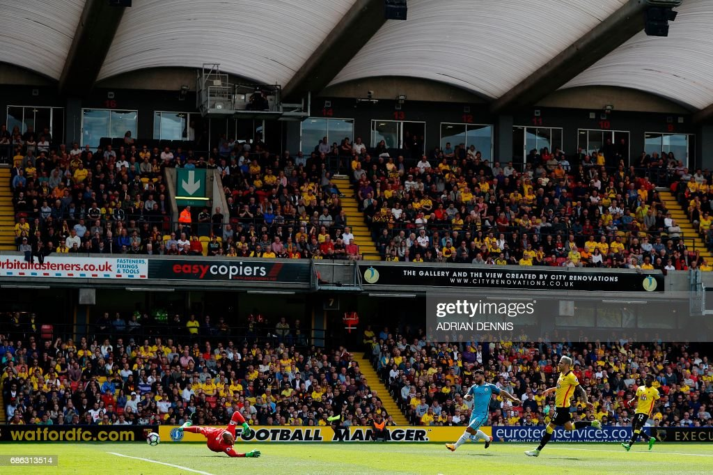 Manchester City's Argentinian striker Sergio Aguero watches the ball after shooting past Watford's Brazilian goalkeeper Heurelho Gomes (L) to scores his team's first goal during the English Premier League football match between Watford and Manchester City at Vicarage Road Stadium in Watford, north of London on May 21, 2017. / AFP PHOTO / Adrian DENNIS / RESTRICTED TO EDITORIAL USE. No use with unauthorized audio, video, data, fixture lists, club/league logos or 'live' services. Online in-match use limited to 75 images, no video emulation. No use in betting, games or single club/league/player publications. /
