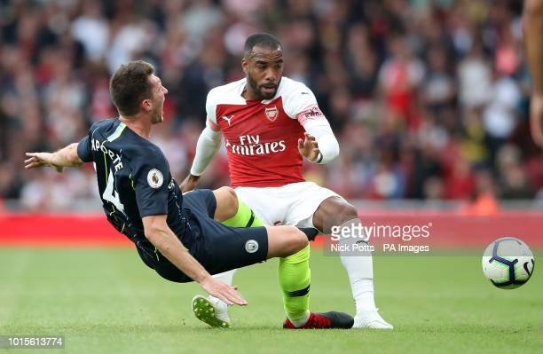Manchester City's Aymeric Laporte and Arsenal's Alexandre Lacazette battle for the ball during the Premier League match at the Emirates Stadium London
