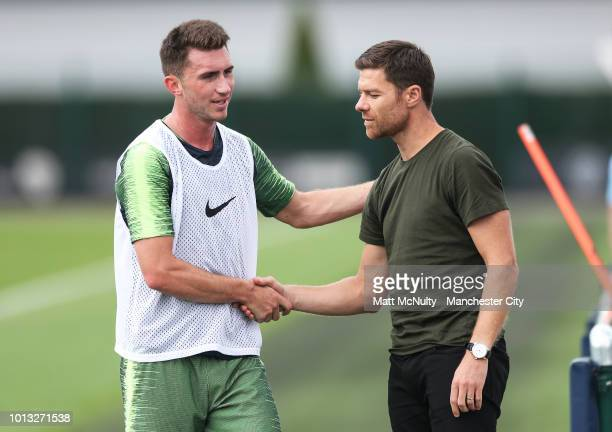 Manchester City's Aymeric Laporte greets Xabi Alonso during training at Manchester City Football Academy on August 8 2018 in Manchester England