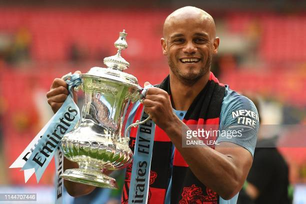 Manchester City's Belgian captain Vincent Kompany holds the winner's trophy after the English FA Cup final football match between Manchester City and...