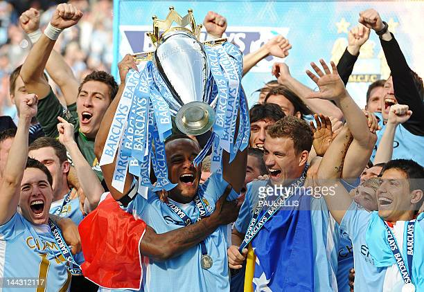 Manchester City's Belgian captain Vincent Kompany lifts the Premier league trophy and celebrates with Bosnian striker Edin Dzeko Argentinian striker...