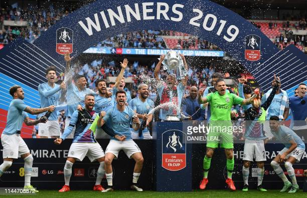 Manchester City's Belgian captain Vincent Kompany lifts the winner's trophy as the players celebrate victory after the English FA Cup final football...