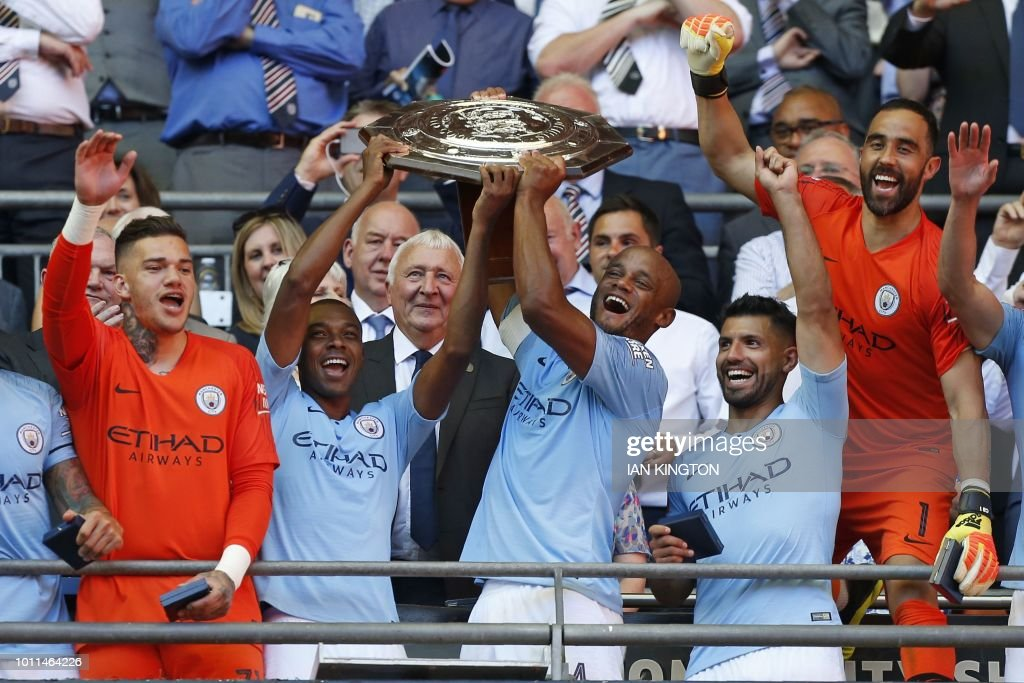 TOPSHOT - Manchester City's Belgian defender Vincent Kompany (centre right) and Manchester City's Brazilian midfielder Fernandinho (centre left) lift the FA Community Shield as Manchester City players celebrate their victory after the English FA Community Shield football match between Chelsea and Manchester City at Wembley Stadium in north London on August 5, 2018. - Manchester City won the game 2-0. (Photo by Ian KINGTON / AFP) / NOT