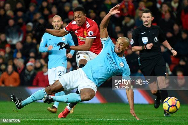 Manchester City's Belgian defender Vincent Kompany dives across to block a shot from Manchester United's French striker Anthony Martial during the...