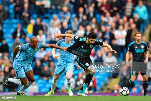 Manchester City's Belgian defender Vincent Kompany hangs on to the shirt of West Bromwich Albion's Argentinian midfielder Claudio Yacob during the...