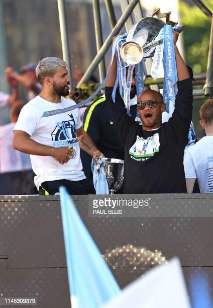 Manchester City's Belgian defender Vincent Kompany holds aloft the Premier League trophy as Manchester City's Argentinian striker Sergio Aguero holds...