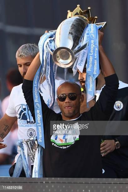 Manchester City's Belgian defender Vincent Kompany holds aloft the Premier League trophy during an opentop bus parade through Manchester northern...