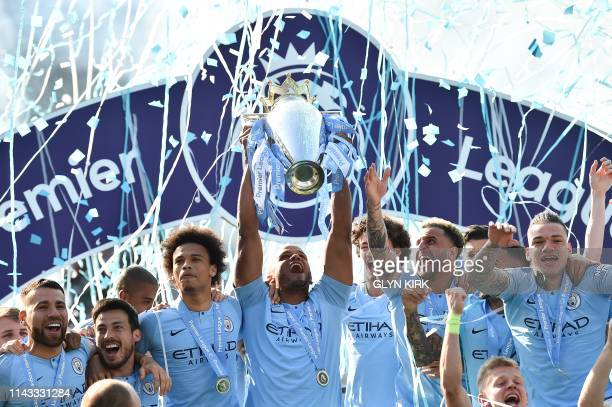 TOPSHOT Manchester City's Belgian defender Vincent Kompany holds up the Premier League trophy after their 41 victory in the English Premier League...
