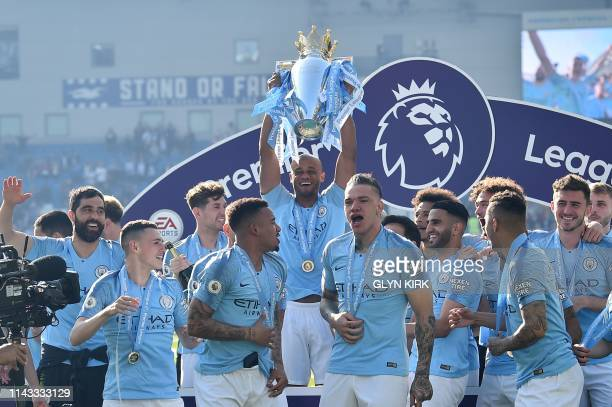 Manchester City's Belgian defender Vincent Kompany holds up the Premier League trophy after their 41 victory in the English Premier League football...