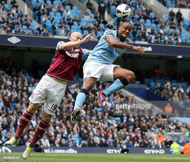 Manchester City's Belgian defender Vincent Kompany jumps to head the ball as West Ham United's Welsh defender James Collins challenges him during the...