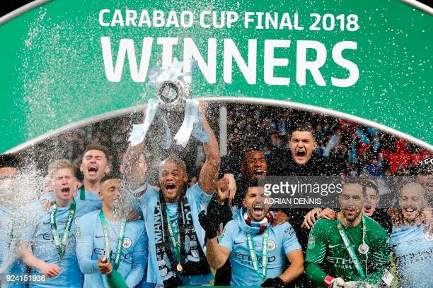 TOPSHOT Manchester City's Belgian defender Vincent Kompany lifts the trophy as Manchester city players celebrate their victory in the English League...