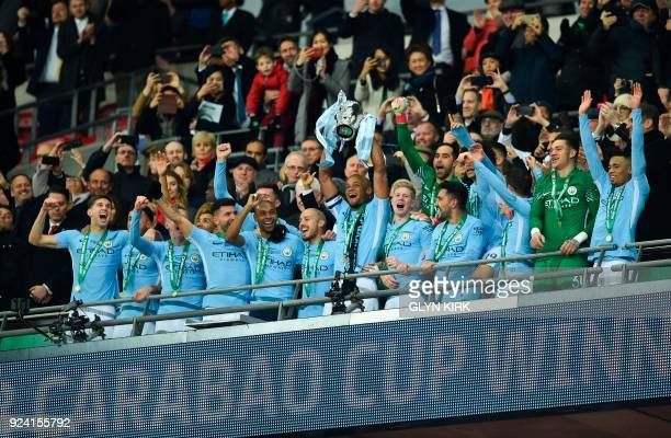 Manchester City's Belgian defender Vincent Kompany lifts the trophy as Manchester city players celebrate their victory in the English League Cup...