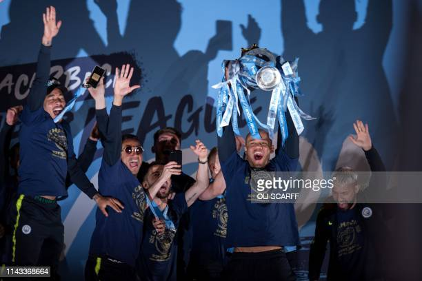 Manchester City's Belgian defender Vincent Kompany shows the Premier League trophy to supporters outside the Etihad Stadium in Manchester northern...