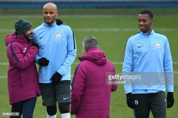 Manchester City's Belgian defender Vincent Kompany stands with a member of the coaching staff during a team training session at the City Football...