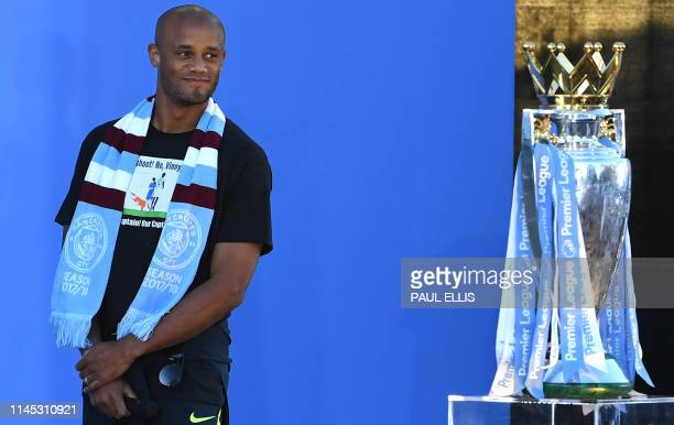 Manchester City's Belgian defender Vincent Kompany stands with the Premiere League trophy during a stage presentation following an opentop bus parade...