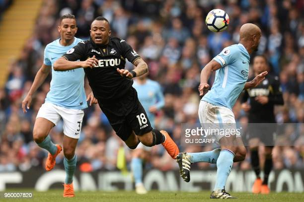 Manchester City's Belgian defender Vincent Kompany vies with Swansea City's Ghanaian striker Jordan Ayew during the English Premier League football...