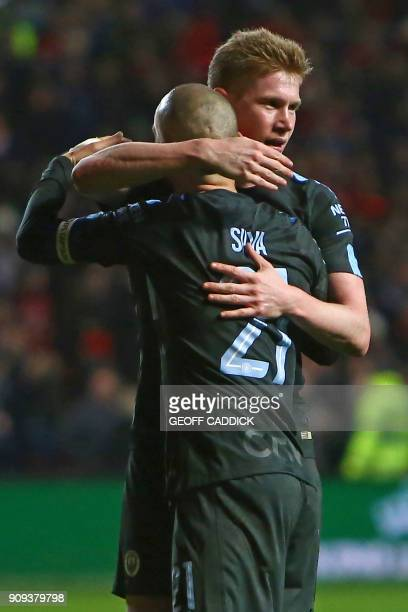 Manchester City's Belgian midfielder Kevin De Bruyne embraces Manchester City's Spanish midfielder David Silva on the pitch as they celebrate after...
