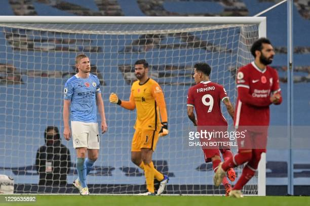 Manchester City's Belgian midfielder Kevin De Bruyne reacts after missing a penalty as Liverpool's Brazilian goalkeeper Alisson Becker looks on...