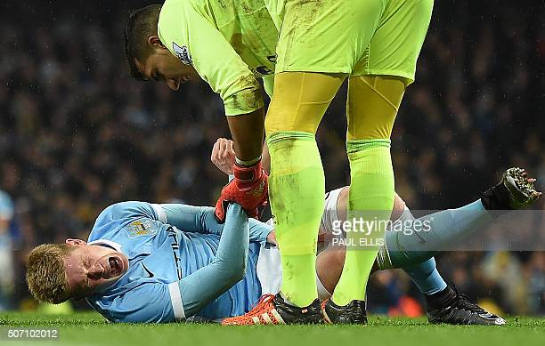 Manchester City's Belgian midfielder Kevin De Bruyne reacts as he talks with Everton's Spanish goalkeeper Joel Robles before being stretchered off...