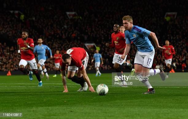 Manchester City's Belgian midfielder Kevin De Bruyne runs past Manchester United's English defender Phil Jones, before striking the ball ball to...